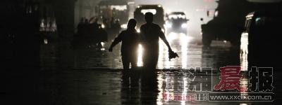 昨晚8点左右,107国道先锋村向公塘组路段,一对情侣试图赤脚通过被淹的道路。本版图片/记者刘有志