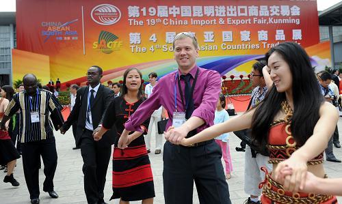 6月6日,一些外国客商和少数民族姑娘一起载歌载舞。新华社记者 蔺以光 摄