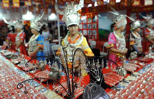 6月6日,一些来自贵州的少数民族姑娘穿着民族服饰推销银饰品。新华社记者 蔺以光 摄