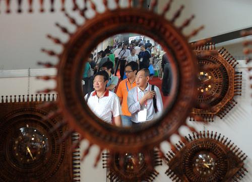 从一个南亚地区生产的镜子工艺品中映射出昆交会上的客商们(6月6日摄)。新华社记者 蔺以光 摄
