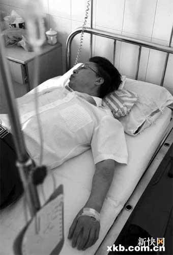 白云区红会医院急诊科原主任唐扩军躺在自己单位的病床上,对于被调职一事他忿忿不平。