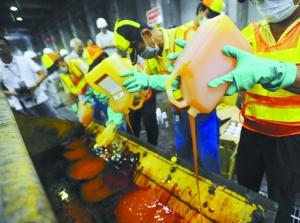 昨日,工作人员在台北木栅垃圾焚化厂将遭塑化剂污染的产品倒入铲车准备焚化处理。新华社发