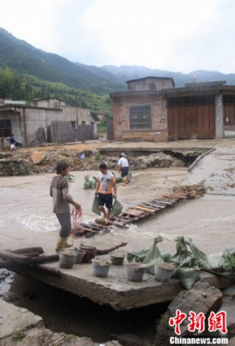 白岭镇_6月14日,在江西修水县洪灾重灾区白岭镇下太清村,几个受灾村民在装填