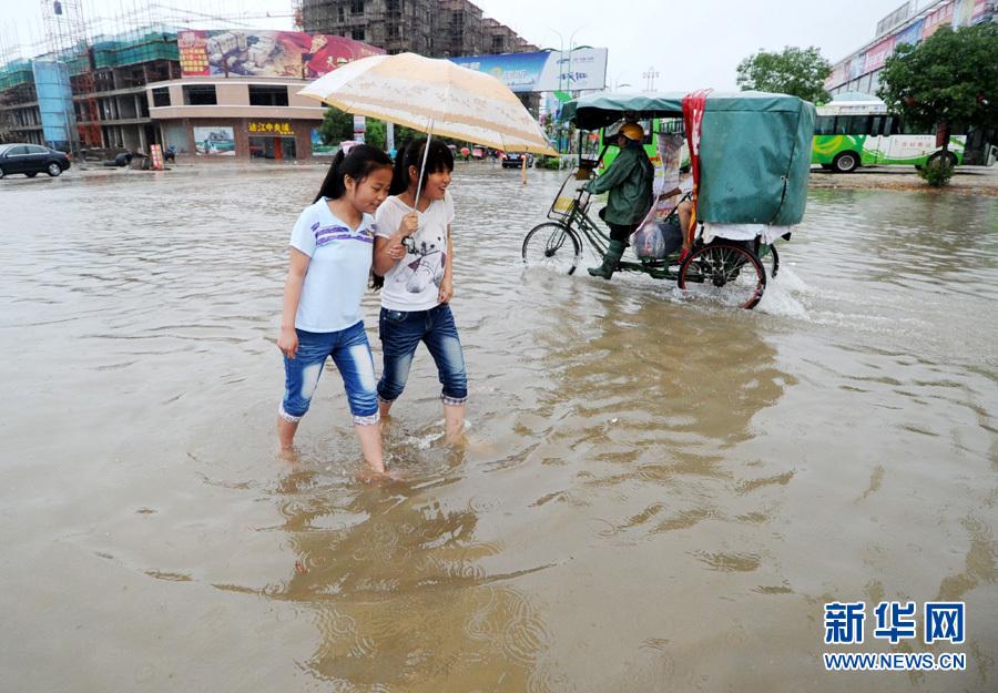 江西余干县两名学生在环城东路积水路面行走