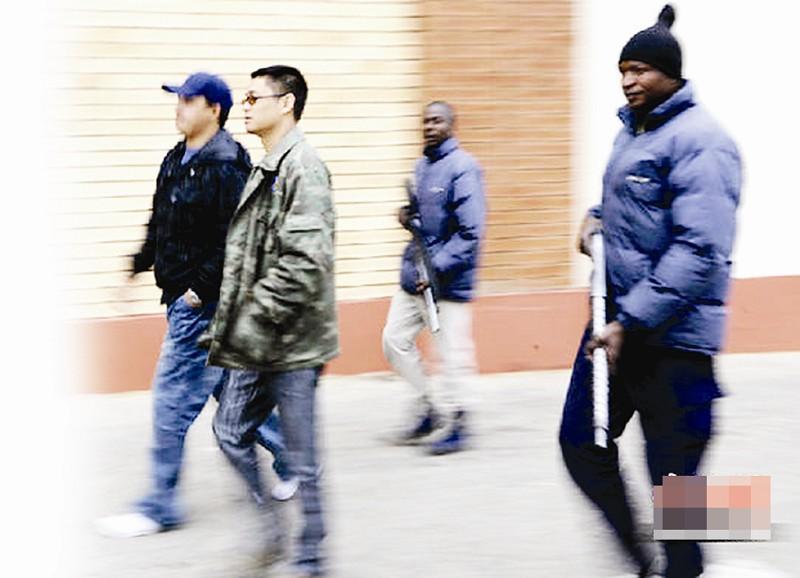 楚天都市报讯 图为:南非华人保安公司总经理谢宇航与南非当地员工持枪在约翰内斯堡中国商贸城内巡逻