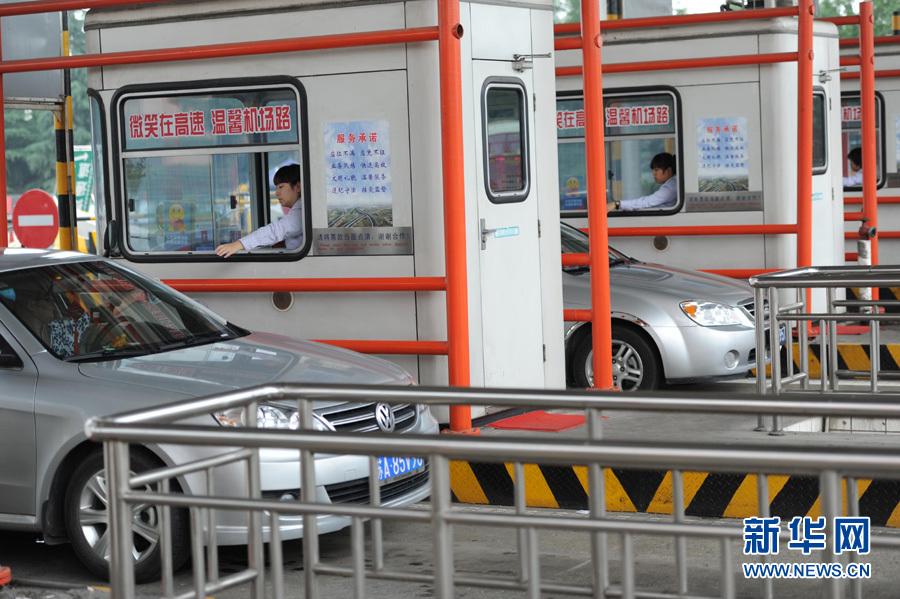 6月19日,南京机场路收费站工作人员在收取过路费.新华社记者韩瑜庆摄