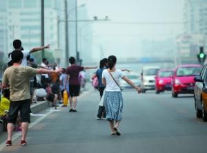公益西桥,不少乘客从地铁站走出,站在路中间打车。
