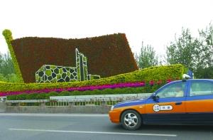 昨日,四元桥,一辆出租车从建党90周年花坛前驶过。本报记者 薛�B 摄