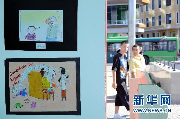 市民从当地儿童手绘的禁烟宣传画前走过