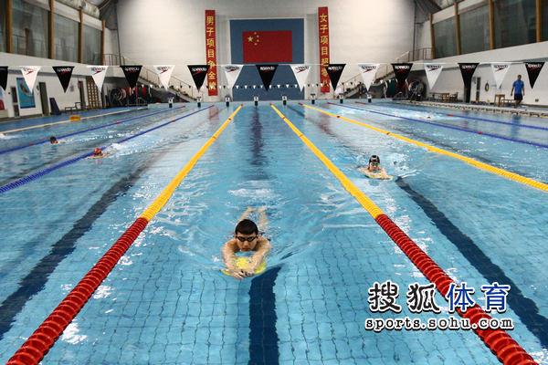 图文:中国游泳队公开训练 男队员借助漂浮物