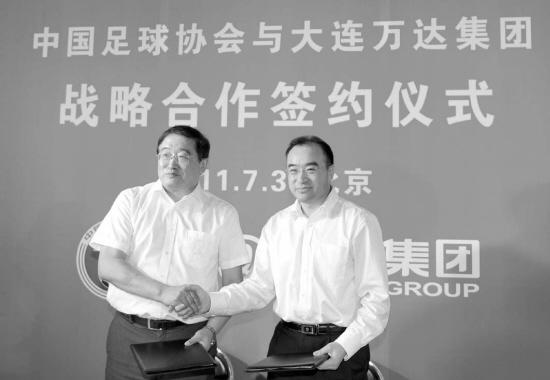 韦迪(左)与万达集团副总裁尹海在签约后握手。新华社发