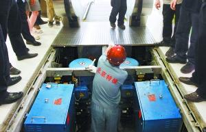 昨天,工作人员检查大型商场手扶电梯的传动设备。本报记者 戴冰摄