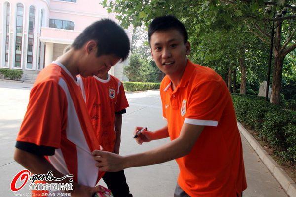 图文:[中超]鲁能小将过生日 为球迷签名