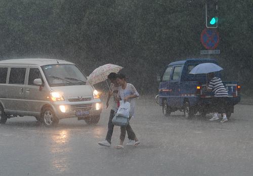 7月11日,合肥市民在暴雨中前行。