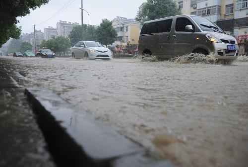 7月11日,车辆在合肥积水的道路上涉水行驶。