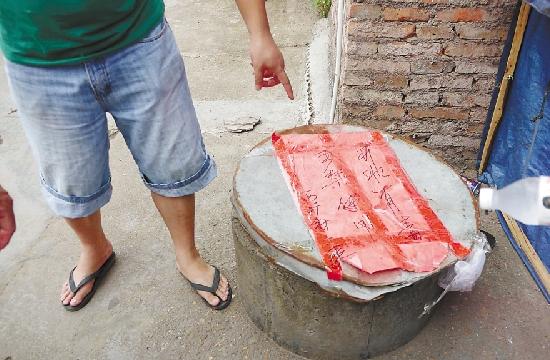 """村里已将两口饮用井用铁皮制的盖子封口,并贴上红纸,写着""""禁止饮用""""几个醒目的大字。(资料图片)"""