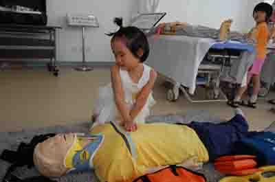 青少年急救夏令营活动中,一个小朋友在感受心肺复苏。虽然力气小,按压不到标准位置,但是急救意识的种子已经种下了。