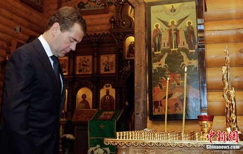7月12日,俄罗斯总统梅德韦杰夫在莫斯科郊区的一座教堂内为沉船事故遇难者默哀。中新社发