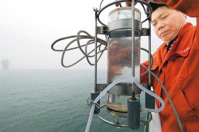 国家海洋局北海环境监测中心工作人员对出现赤潮海域采取水样。