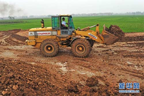 一辆装载机在湖北省襄阳市襄州区双沟工业园9号路上挖土