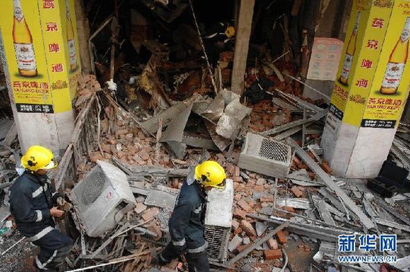 7月26日,澳门消防队人员在现场探勘。当日,澳门新口岸区国际中心大厦一地铺餐馆怀疑因气体泄漏引发爆炸,13人受伤。新华社记者 张金加