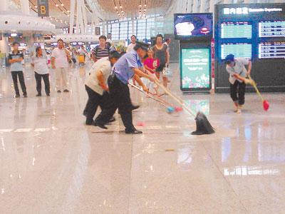 7月19日,新运营的长沙黄花机场T2航站楼漏水如瀑布,出发厅一号出口处,旅客撑伞从室内慌忙奔出,屋顶严重漏水,工作人员在大厅清扫积水。      读者 怡然真仔 供图