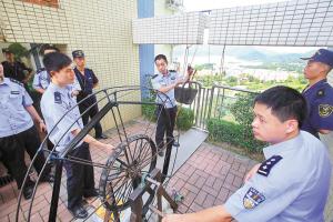 """3办案民警演示犯罪分子通过手动摇动绞盘,""""飞线""""转动,将走私品从香港运到深圳。"""