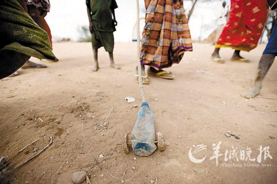 难民营儿童在玩用塑料瓶做成的玩具车