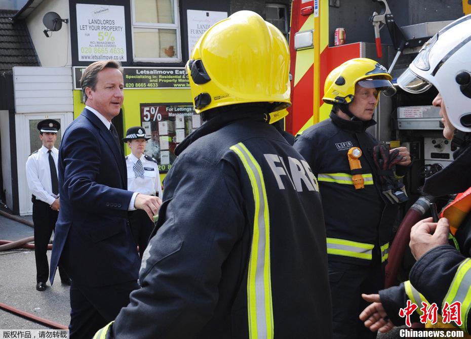 2011年8月9日,英国首相卡梅伦来到位于伦敦南部的克罗伊登市,与警察及消防员会面,了解情况。他在警方人员的陪同下,视察了多栋被烧毁的建筑物。(中新网)