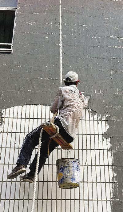 汗流浃背的粉墙工正在悬空作业