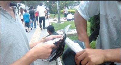 黄牛从包里掏出门票。本报记者 苏晓明 摄