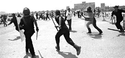 15日,在庭审现场外,警察驱赶骚乱的人群。 新华社发