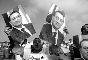 支持者高举穆巴拉克肖像参加游行。新华社发