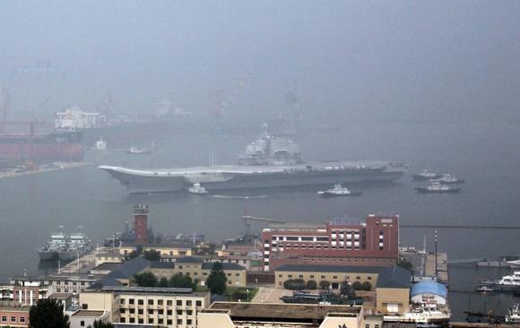 2011年8月14日,大连,中国航母平台在7艘拖船的簇拥下穿过浓雾返回港口。