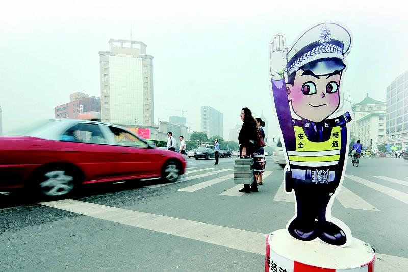 """25日,太原市交警部门将近百块""""卡通警察""""放置在市区各主要交通路口,温馨提示过往车辆和行人遵守交通规则,注意交通安全。"""