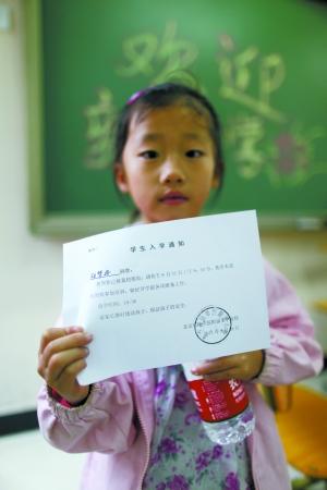 一名打工子弟学校分流来的小学生拿到了入学通知书。