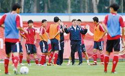 主教练卡马乔(右四)给队员们讲解技战术。
