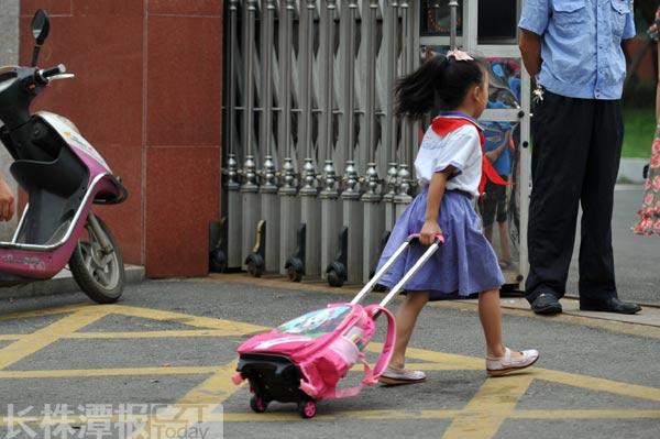 一位小学生拉着书包进校门