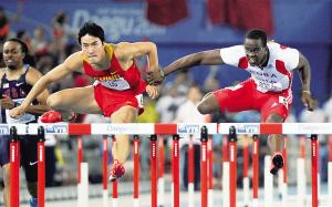 29日,古巴选手罗伯斯(右)在决赛中用手扒住中国选手刘翔的手腕。 新华社发