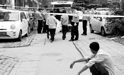 事故现场被封锁,尸体被抬出.本报记者 杨天啸 摄