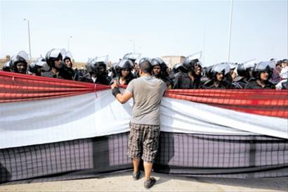 9月5日,在埃及开罗警察学院外,一名埃及前总统穆巴拉克的反对者同警察交谈。新华社记者 李木子 摄