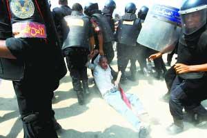 9月5日,在埃及开罗警察学院外,埃及防暴警察在冲突中控制一名穆巴拉克的反对者。 新华社/法新