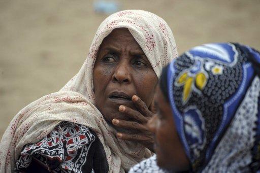 10日的图显示,坦桑尼亚警方抱着一些船难中年幼遇难者的遗体