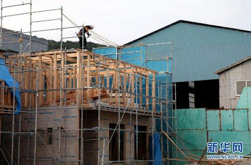 在日本宫城县石卷市,施工人员在受灾住宅原址修建新楼。(9月8日摄)