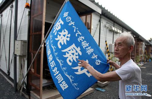 在日本宫城县女川第一小学校园内的临时安置房,年过八旬的阿部宗锐在房前打出一面反对女川核电站的旗帜。女川核电站震后停运至今。(9月8日摄)