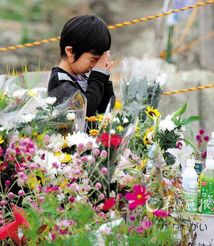 11日,一个日本男孩为逝去的亲人祈祷