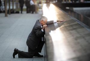 """今年9月11日是美国遭遇""""9·11""""恐怖袭击十周年。图为在美国纽约世界贸易中心遗址""""9·11""""纪念园,一位父亲注视着恐袭中罹难儿子的名字。新华社/法新"""