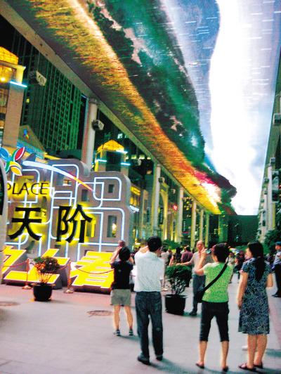 """37岁的蒲坤先生,在北京从事设计行业,只要有空就带着儿子来世贸天阶。他指着头顶的屏幕说:""""全靠这块屏给这里带来无限的商机和人气。"""""""