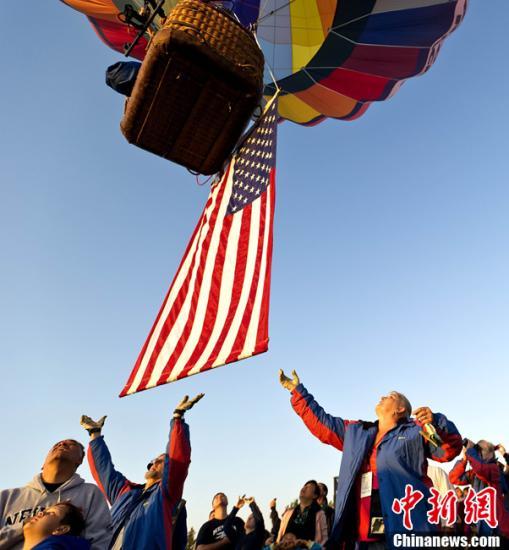 """当地时间9月10日,美国多个城市举行活动,纪念""""9·11""""十周年。图为内华达州雷诺市民众清晨用热气球升起美国国旗。中新社发 陈钢 摄"""