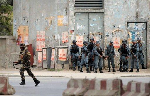 当地时间13日,阿富汗安全部队在喀布尔与攻击使馆区的塔利班武装分子交火,图为安全部队在交火建筑附近站岗。